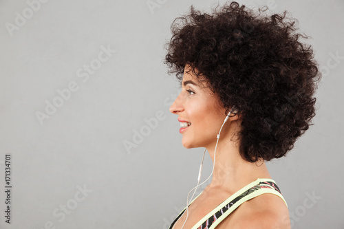 Portrait in profile of curly fitness woman listening music - 171334701