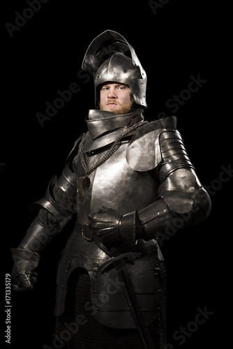 Knight in armour after battle on the black background Canvas Print
