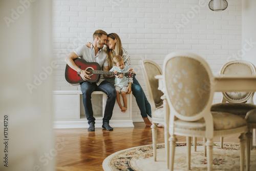 Plakat Urocza młoda para z gitarą w pokoju