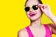 Leinwandbild Motiv Beautiful cheerful cheerful young girl in sunglasses wearing yellow glasses on a yellow background laughing. Healthy white teeth, pink lipstick and nails. Pink T-shirt. Studio on a yellow brigh. Fun.