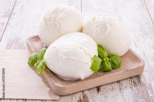 Tre mozzarelle intere di latte di bufala in un piatto di legno isolate su un tavolo