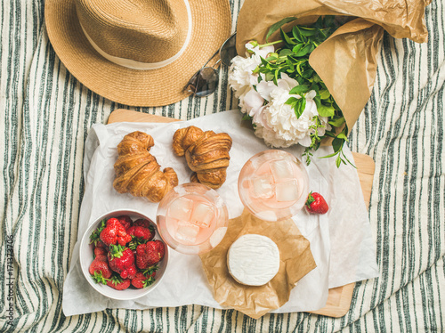 Keuken foto achterwand French style summer outdoor picnic setting. Flat-lay of glasses of rose wine, strawberries, croissants, brie cheese on board, straw hat, sunglasses, peony flowers, top view. Outdoor gathering concept