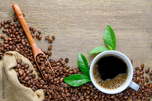 Coffee cup with beans, wood spoon, hemp sack bag and green leaf on wood table