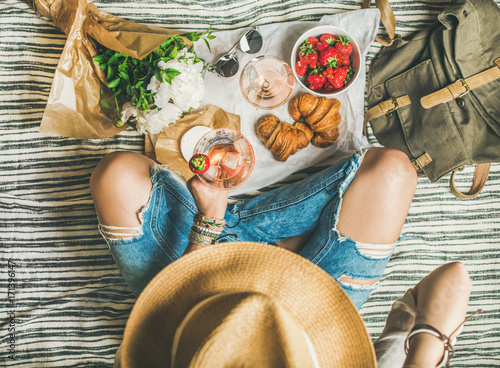Keuken foto achterwand French style romantic picnic setting. Woman in shabby jeans and hat with glass of ice rose wine, strawberries, croissants, brie cheese, sunglasses, peony flowers, top view. Outdoor gathering concept