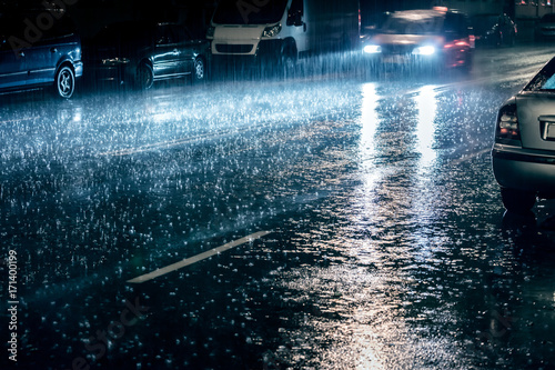 Fotobehang Tokyo car in motion with switched on headlights driving during heavy rain