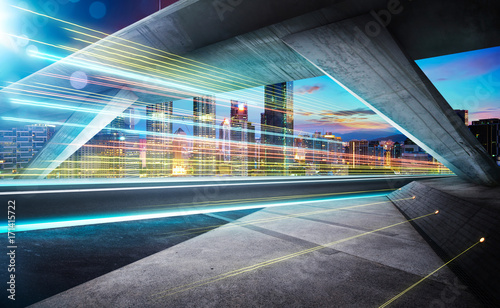 Photographie  Empty asphalt road under the bridge during the night with light trails and beautiful city skyline background