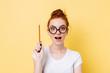 Happy ginger woman in eyeglasses having idea