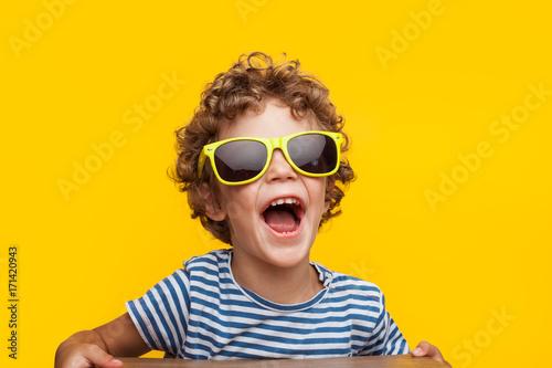 Adorable kid in bright sunglasses on orange Fototapet
