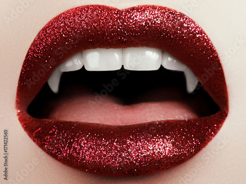 Foto Female lips with glittering red lipstick, vampire teeth
