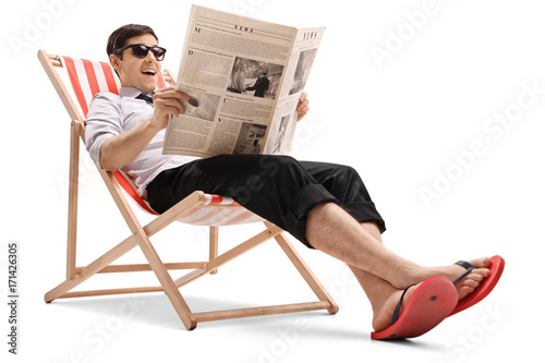 Businessman sitting in a deck chair and reading a newspaper Fototapete