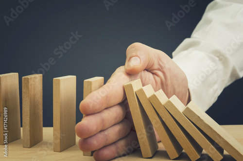 Fotografía Businessman halting the domino effect inserting his hand between falling and upr
