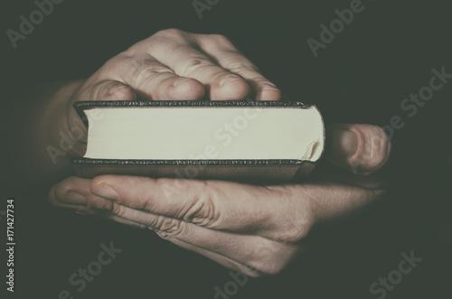 Fotografie, Obraz  Holy Bible in man`s hands closeup. Low key image.