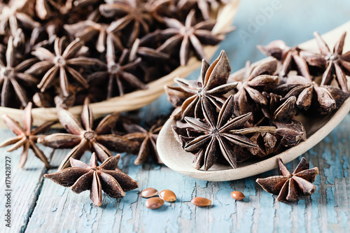 Whole star anise in a basket and spoon on wooden background