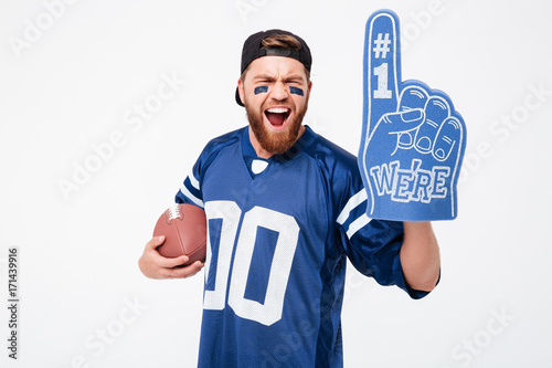 Photo Excited man fan wearing fan glove holding rugby ball.