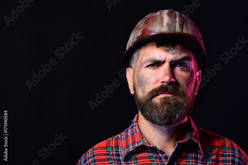 Fotografía  Worker with brutal image wears dirty helmet and plaid shirt