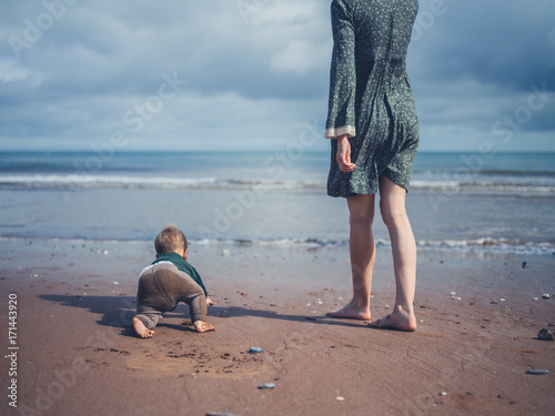 Mother on beach with baby crawling into sea