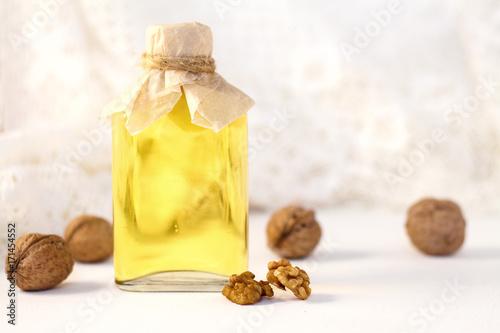 Valokuva  Walnut oil in bottle on white wooden background. Selective focus.