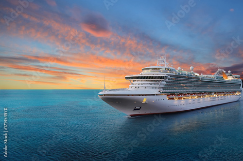 Fototapeta Luxury cruise ship sailing to port on sunrise