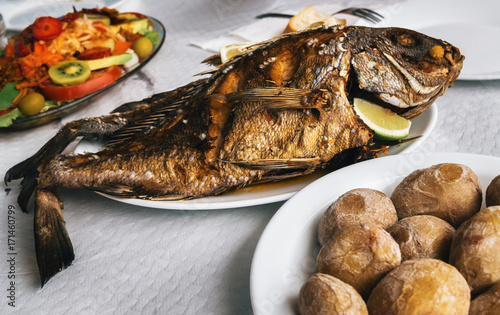 Keuken foto achterwand Canarische Eilanden Grilled fish on plate, canarian wrinkly potatoes and salad with vegetables and fruits. Tenerife, Canary islands
