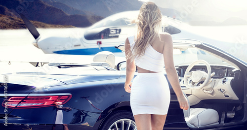 Fotografía  Sexy woman with luxury car and airplane.