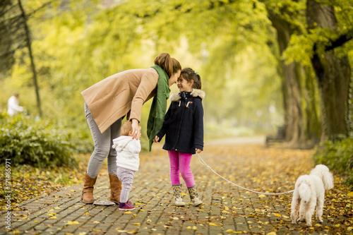 Zdjęcie XXL Matka i dwie dziewczyny spaceru z psem w parku jesienią