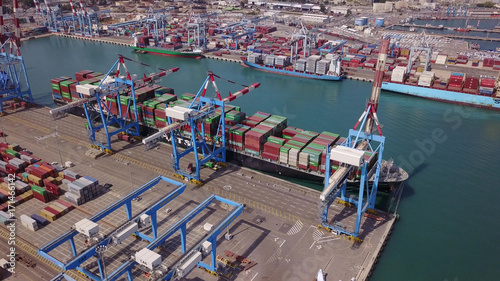 Fully loaded container ship docked at freight port terminal