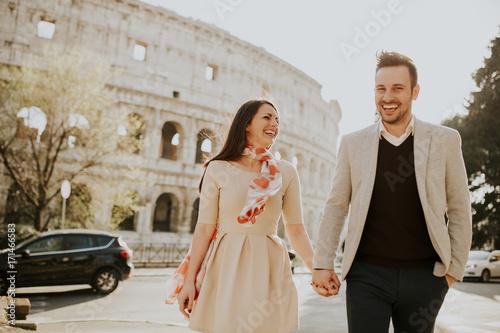 Fotografie, Tablou  Loving couple visiting Italian famous landmarks Colosseum in Rome, Italy