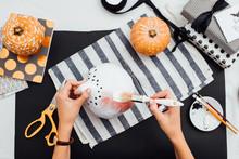Woman Painting Halloween Pumkins