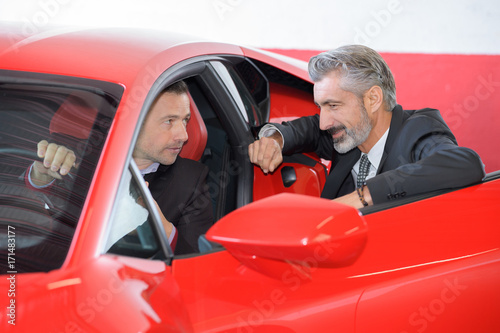 Photo seller and rich customer discussing the ferrari performances