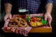 мужчина несет разнос с пивом,колбасками гриль и кренделем