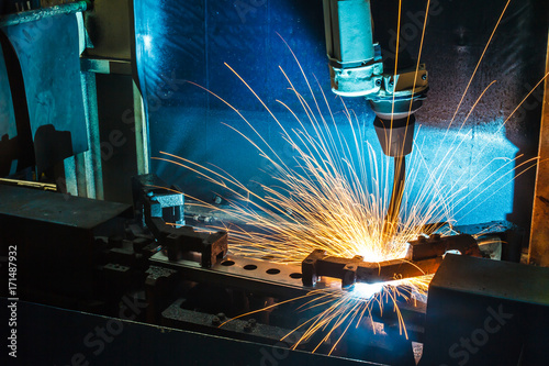Fotografía Worker, welding in a car factory with sparks, manufacturing, industry