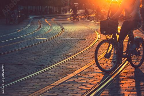 Plakat Zamazujący ludzie jedzie bicykl podczas zmierzchu w mieście Bordo w rocznika stylu i zbożowa tekstura z kopii przestrzenią