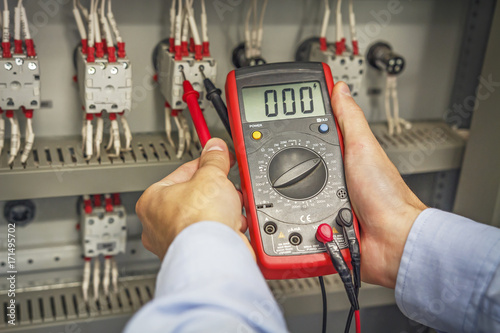 engineer s hands with multimeter close up against background of
