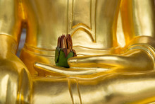 Close-up Detail Of A Golden Statue Of Lord Buddha In The Bhumisparsha Mudra Sitting Position, With A Flower Offering In The Palm Of His Hand. Uthai Thani, Thailand. Travel And Religion Concept.