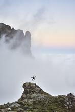 Joyful Pumping From A Rock Peak In Majestic Misty Mountain Surroundings.