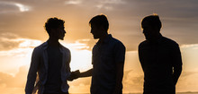Silhouette Of Three Young Men At The Beach At Sunset