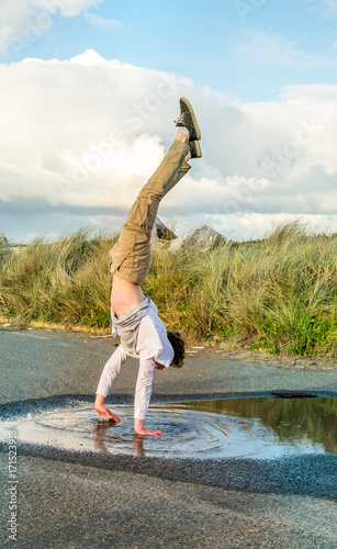 Young man doing a handstand in a puddle of water Wallpaper Mural