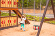 go on the swings. Kid playing on a swing set. Public child's swing-set at a playground. There are also other gaming devices. Children's playground in park. Healthy and active childhood concept.