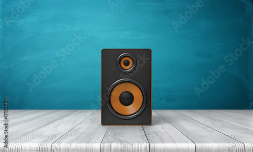 Fotografía 3d rendering of a one black speaker box with orange trim standing on a wooden table in front of a blue background