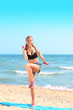 Sporty young woman training on sea beach