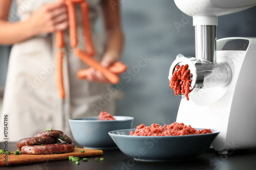 Papiers peints Viande Meat grinder with fresh forcemeat and woman holding sausages in kitchen