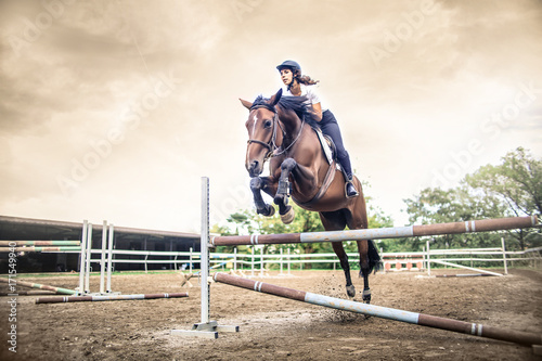 Girl riding a horse, jumping over an obstacle