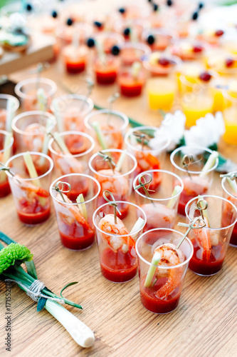 Beautiful lines of different alcohol and non-alcohol cocktails. Snack cocktails with tomato juice and shrimps. Vertical photo. Catering table for party.
