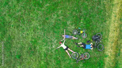 Tuinposter Ontspanning Family cycling on bikes outdoors aerial view from above, happy active parents with child have fun and relax on grass, family sport and fitness