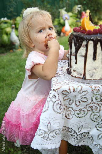 A little white-haired girl of two years is trying a birthday cake. Little ccc3be9a7