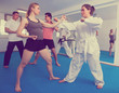 Adults are practicing new karate moves in pairs