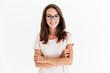 Smiling brunette woman in eyeglasses posing with crossed arms