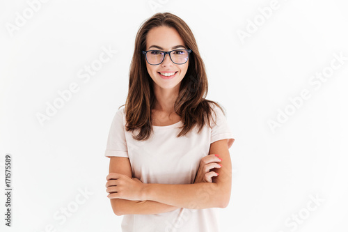 Obraz Smiling brunette woman in eyeglasses posing with crossed arms - fototapety do salonu