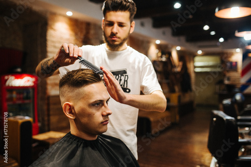 Fotografie, Obraz  Barber is combing the client's hair comb