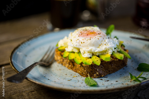 Black bread toast with fried benedict egg, avocado and salmon spread in blue pla Canvas Print